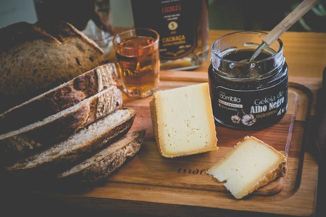 tábua com pão, queijo, geleia de alho negro e cachaça