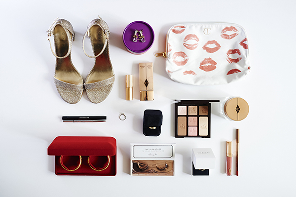 Flatlay featuring Stuart Weitzman gold bridal sandals, Kate Spade earrings, Charlotte Tilbury and Dior makeup, Tiffany men's gold wedding band, De Beers half pave infinity wedding band, Esqido false eyelashes