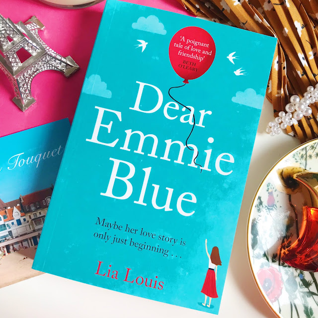 Dear Emmie Blue by Lia Louis book. Pink background, flower dish to the right with perfume on top