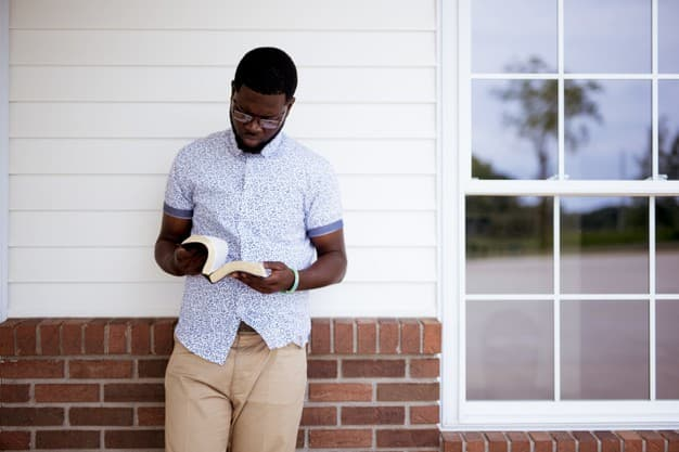 A imagem mostra um homem encostado na parede enquanto le a biblia