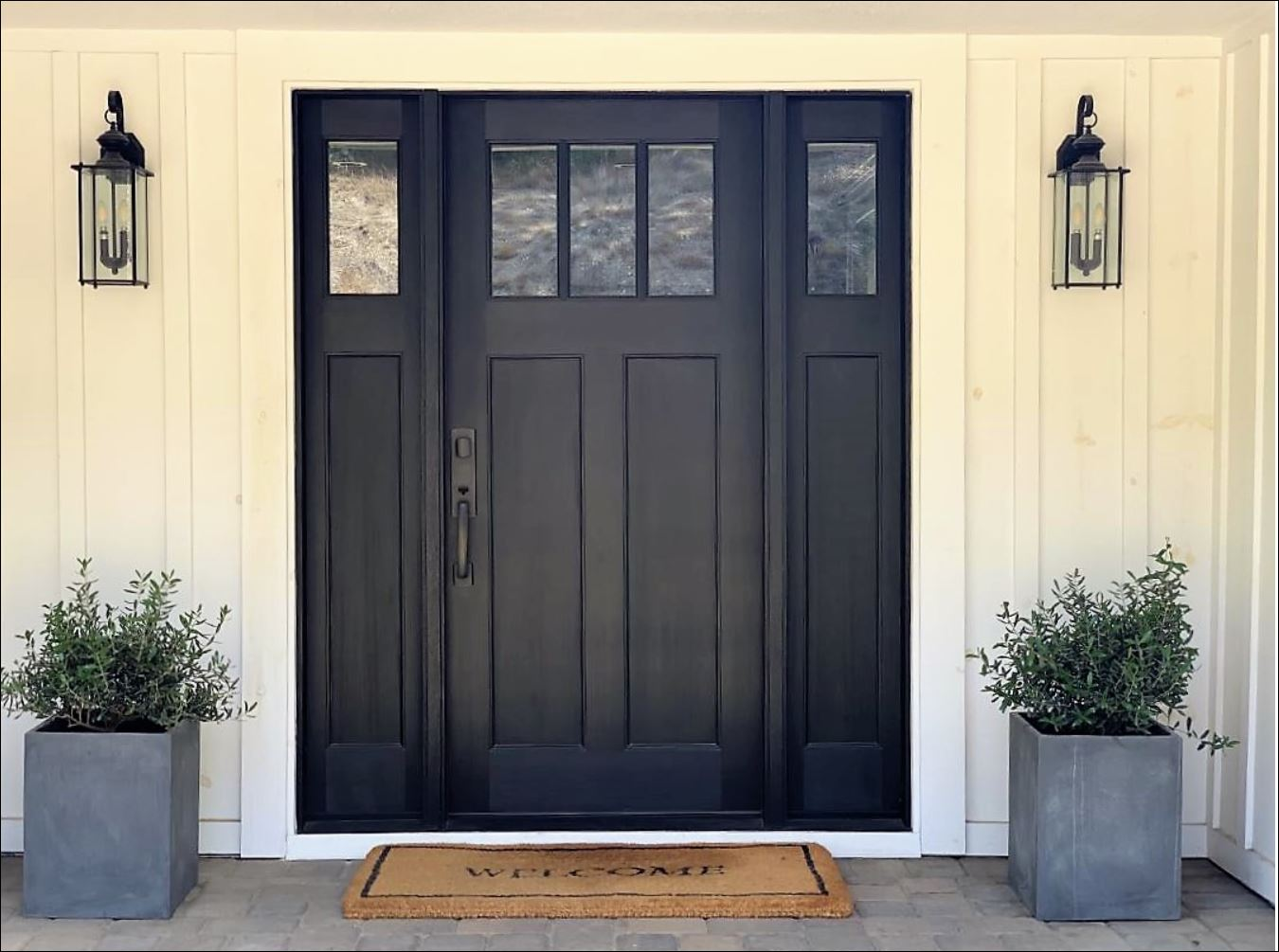 mid-century ranch house exterior home remodel and improvements drought-tolerant plants landscape pavers stone pea gravel black craftsman entry door privacy gate board and batten black and white