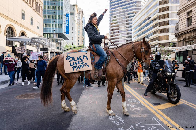 Brianna Noble on her Horse in front of a crowd of protestors.
