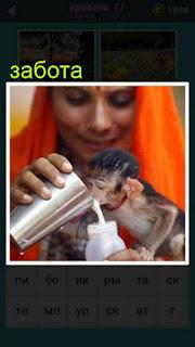 женщина заботится о мартышке, давая ей пить молоко из стакана