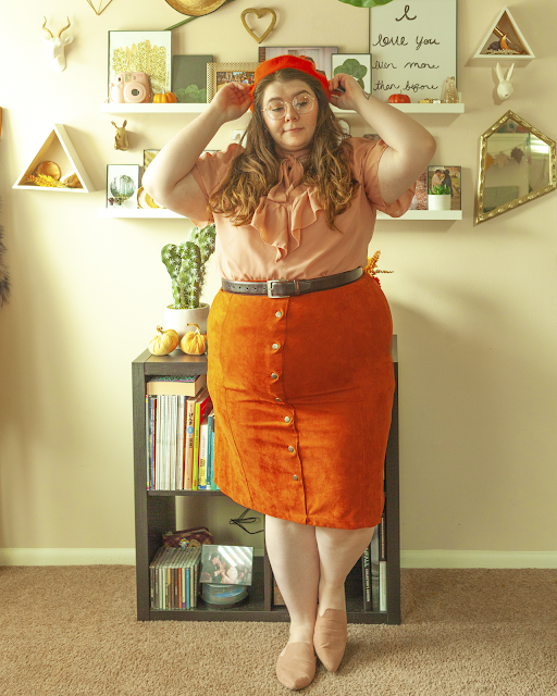 An outfit consisting of an orange beret, a short sleeve pastel pink blouse with a tie beck and ruffles on the bodice, tucked into a burnt orange button down midi skirt and pointed toe muted pink mules.