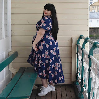 Plus size woman with long black hair wearing floral dress