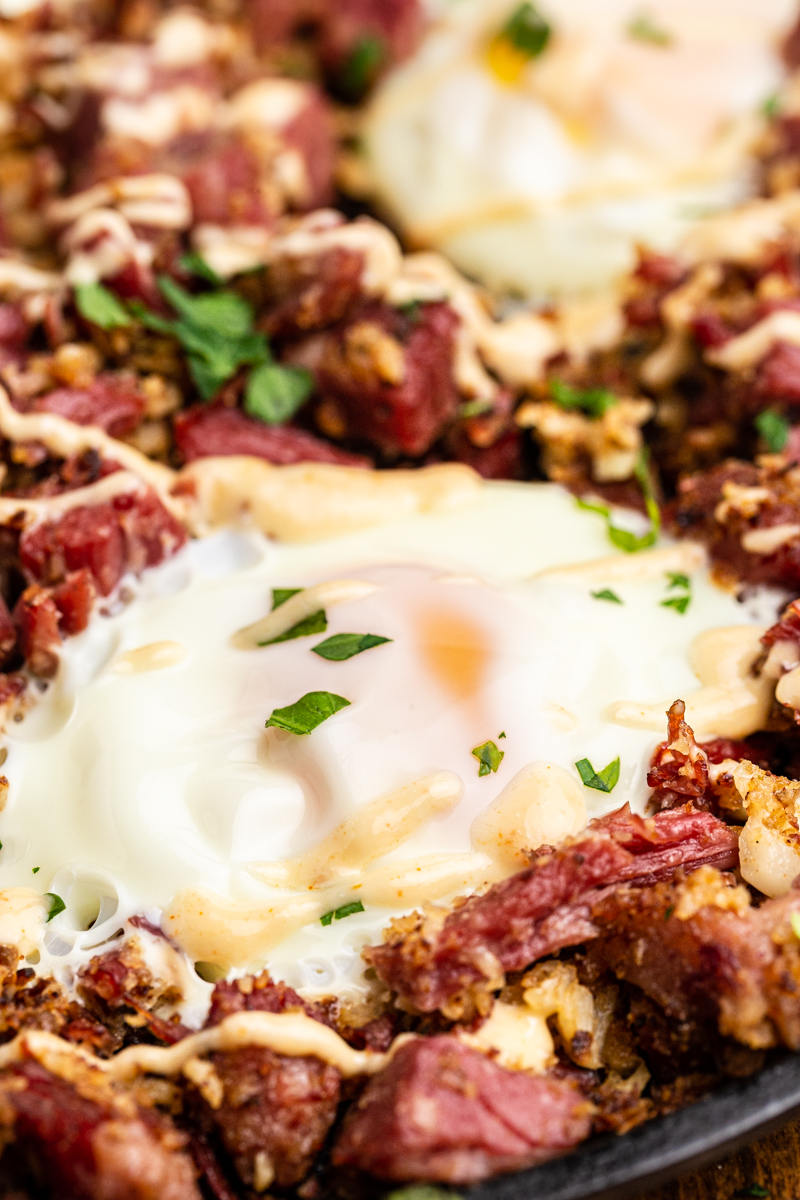 Coseup photo of keto corned beef hash in a skillet with a fried egg and Russian dressing on top.
