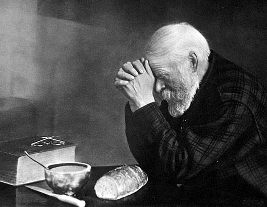 Elderly man with hands folded, saying a prayer over a table with a simple meal