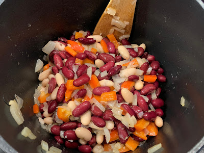 Beans, onion, red pepper and herbs in a saucepan