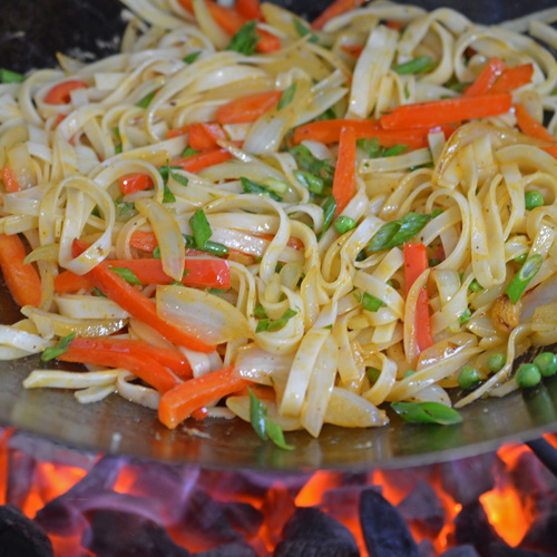 Cooking stir-fried noodles in a wok on the Big Green Egg kamado grill