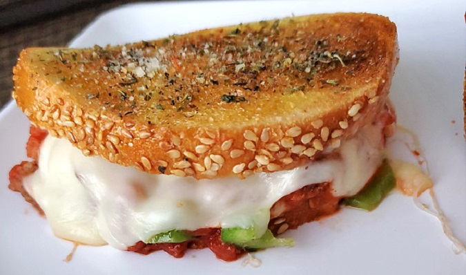 this is two pieces of Italian bread with sesame seeds on the edges the middle has provolone and melted mozzarella cheese with sloppy joe mixture in the middle