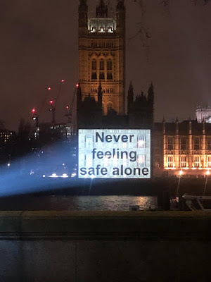 "A message projected onto the Houses of Parliament: ""Never feeling safe alone""."