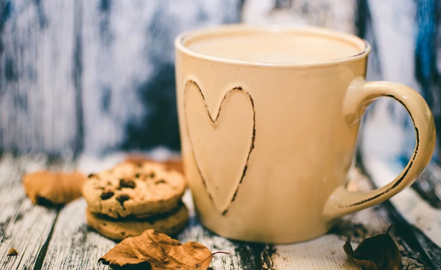 A cup of coffee and a pile of chocolate chip cookies.