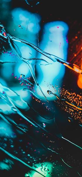 خلفية خطوط ماء تنساب على سطح زجاجي بضوء أزرق داكن
