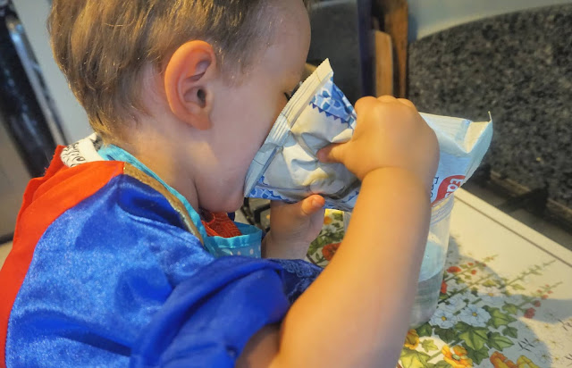 toddler pouring in easiyo yoghurt mix to container