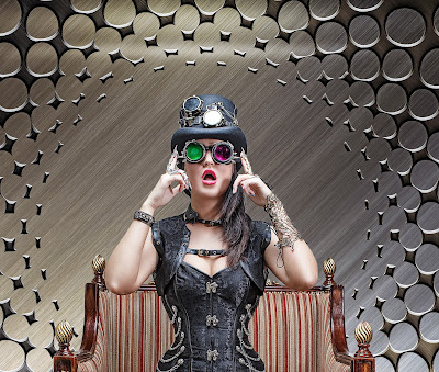 A steampunk woman sits in a 19th century style chair.