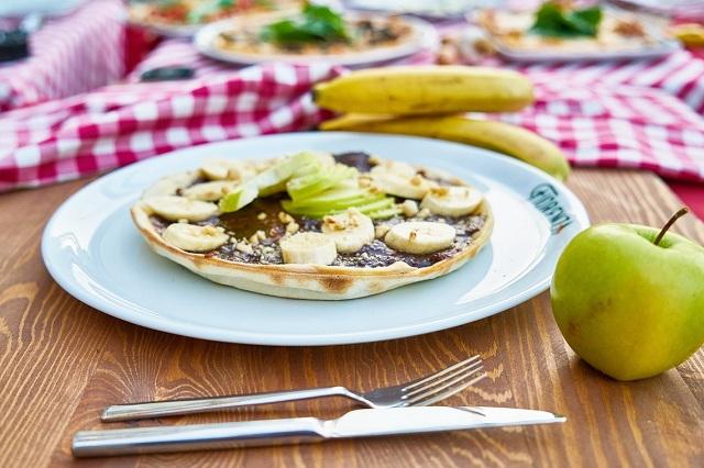 mesa con plato de pizza de chocolate y una manzana