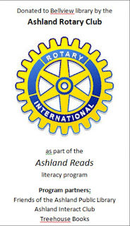 Book-plate design combining black text with the yellow and blue spoke-and-wheel logo of Rotary International, against white background. Text reads: 'Donated to Bellview library by the Ashland Rotary Club as part of the Ashland Reads literacy program. Program partners: Friends of the Ashland Public Library. Ashland Interact Club. Treehouse Books'
