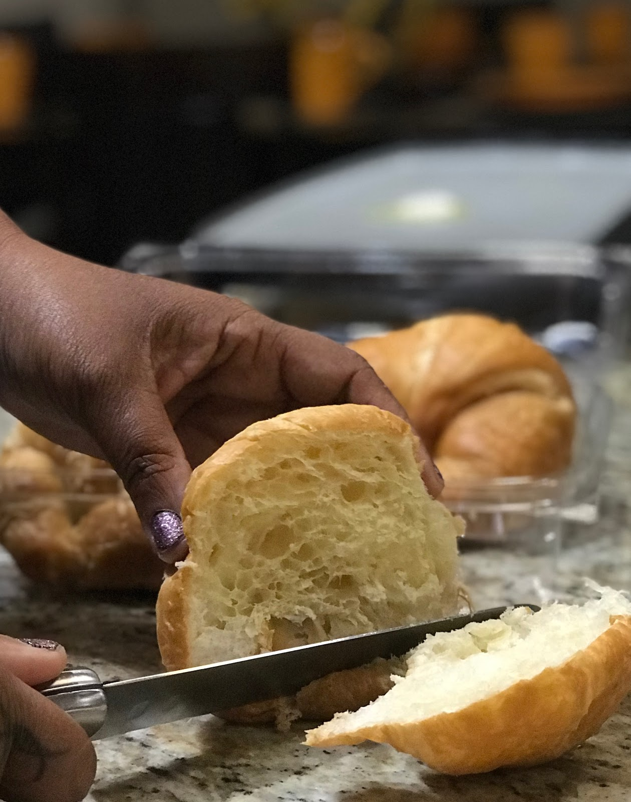 Tangie Bell cutting up croissant bread to make sweet fried pear croissant sandwich