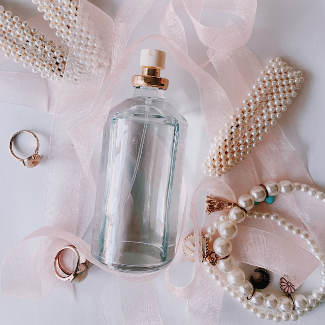 Women's accessories (pearls, gold rings) and perfume on flatlay display.