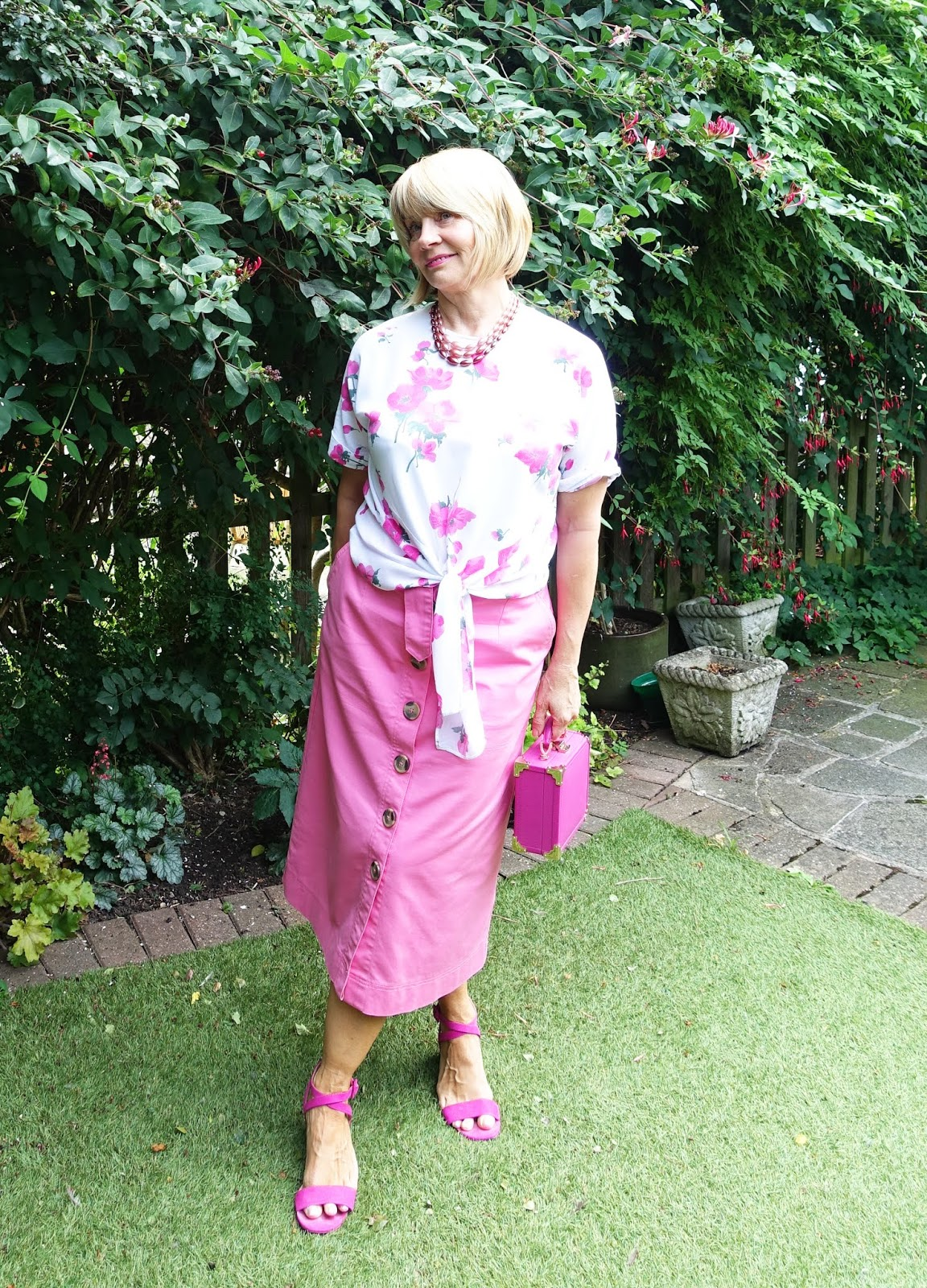 Millennial pink midi skirt, sandals and rose print blouse worn by over-50s blogger Gail Hanlon at Is This Mutton