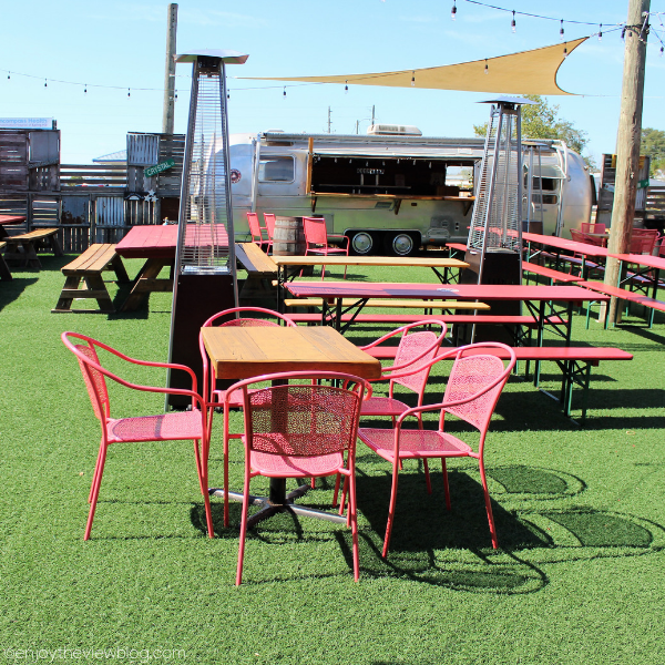 beer garden with picnic tables and a bar in a bus