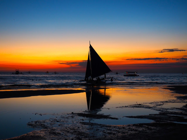 Sail boat silhouette with reflection at sunset on White Beach, Boracay, Philippines