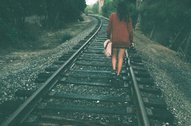 Mulher nova andando nos trilhos de um trem