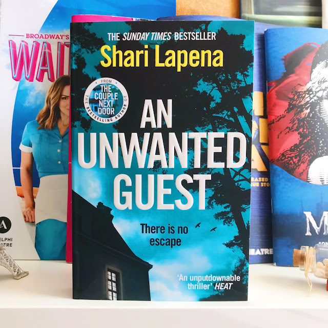 An Unwanted Guest by Shari Lapena book on desk, musical programs in background