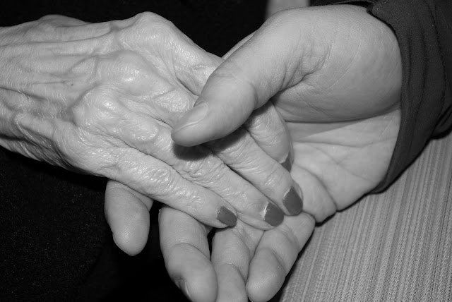 close up of 2 people holding hands one hand is old and wrinkled the other is a younger adult
