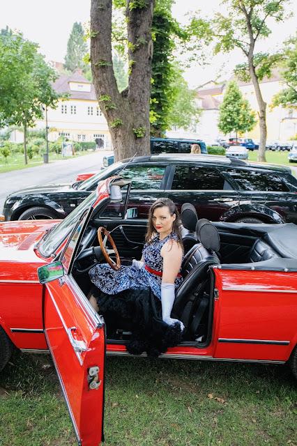 Christina Palfy in einem Kleid von boutique new vintage in einem roten oldtimer sitzend bei rocknroll im kurpark Bad Sauerbrunn