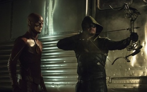 Grant Gustin as The Flash and Stephen Amell as The Arrow standing together by a train facing the same direction poised for action