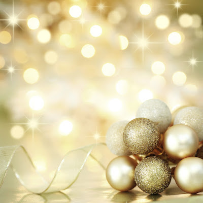 gold glimmering background with gold sphere holiday ornaments and a gold ribbon