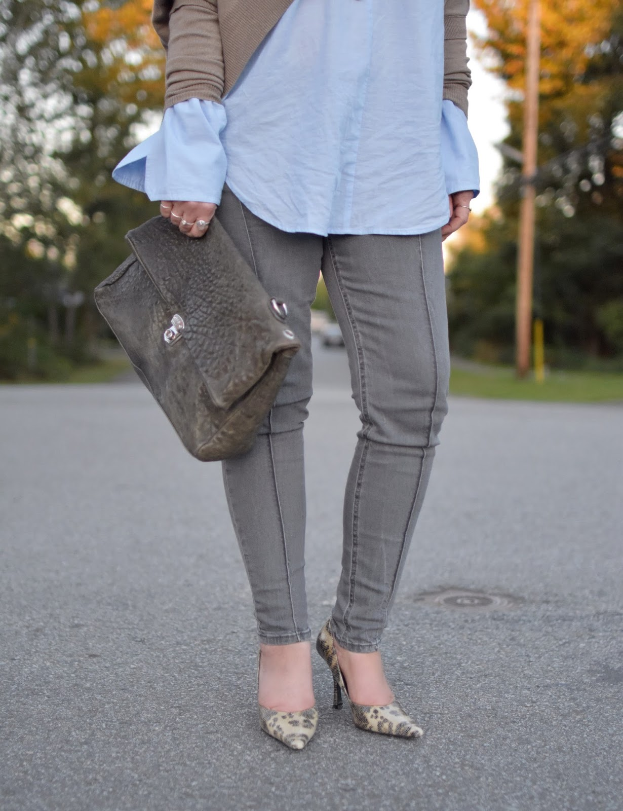 drapey shrug, oversize-cuffed shirt, grey skinny jeans, reptile-patterned pumps, slate blue satchel
