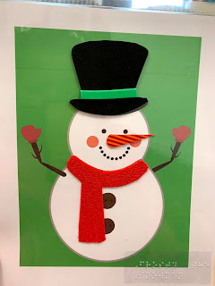 A green background with a while snowman wearing a hat and scarf with tactile on those parts
