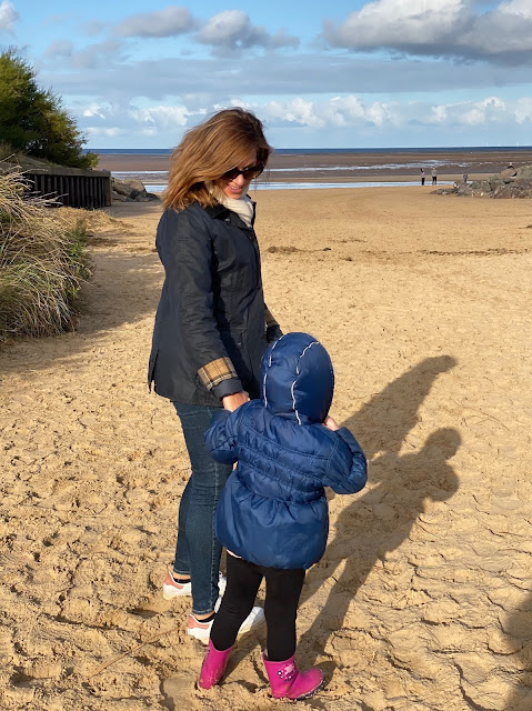 A woman with brown hair (auntie Clare) holding the hand on a 3 year old (Little) on a sandy beach with sand dunes visible at Brancaster Norfolk