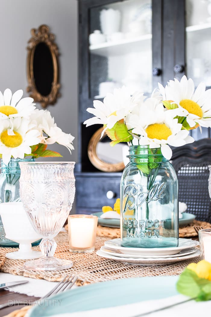 white and yellow daisies in blue mason jars