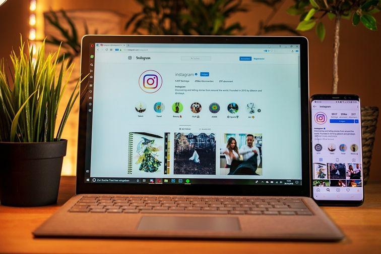 Computador e celular com perfil do Instagram.