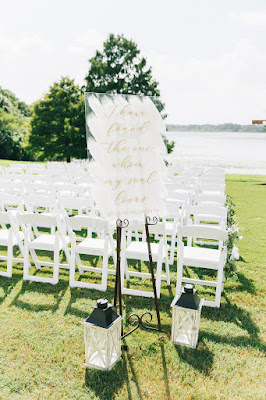 white welcome sign and lanterns at ceremony