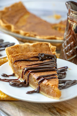 slice of baked peanut butter pie with hot fudge on plate with rest of pie behind it