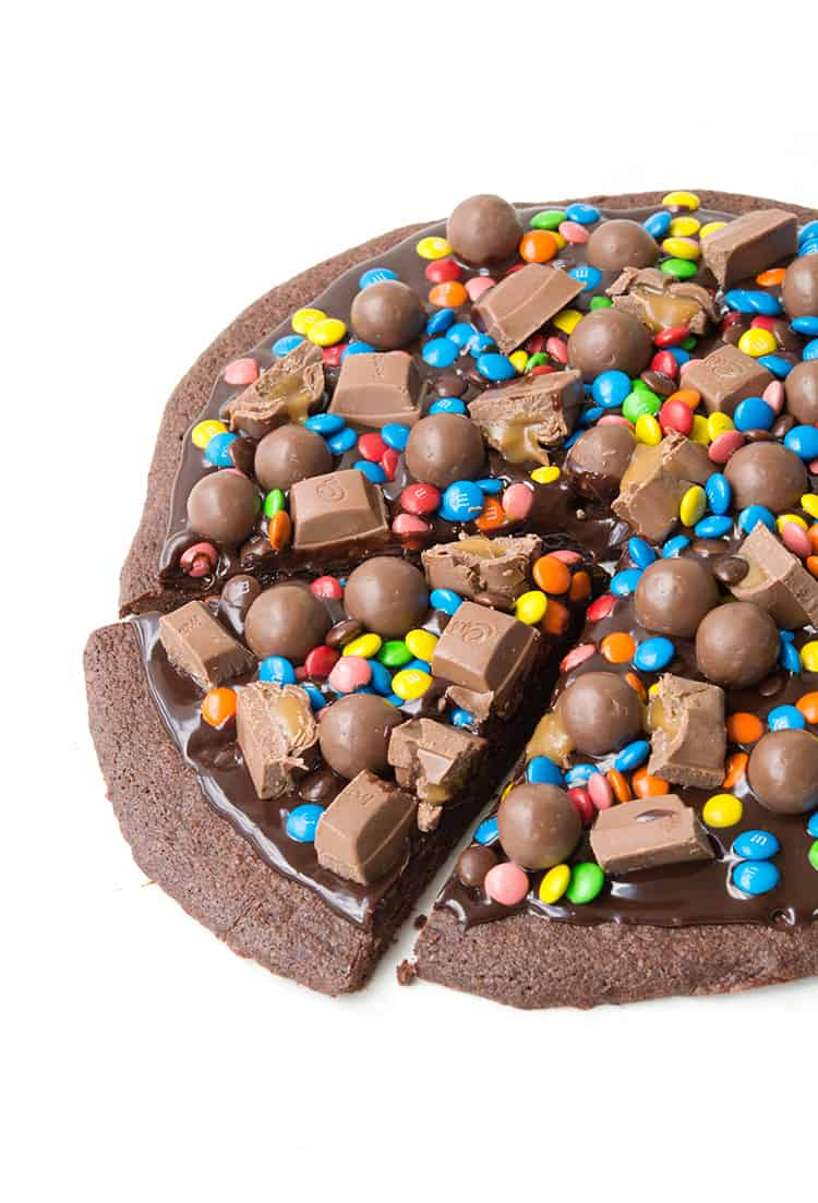 M&M Chocolate Brownie Pizza - Delicious chocolate brownie pizza covered in a chocolate ganache sauce, M&M's, Maltesers and caramel chocolates.