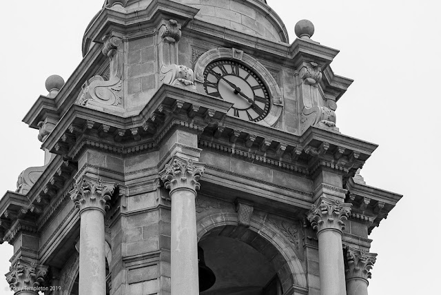 Portland, Maine USA April 2019 photo by Corey Templeton. A black and white close up of the City Hall clock tower on a grey day.