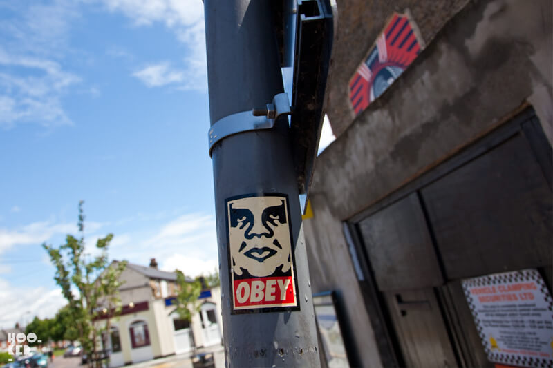 Shepard Fairey Sticker on a lamp post in North London next to his London mural