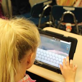 Girl at a desk looking at an iPad