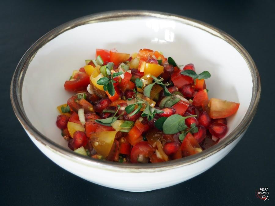 Fresca y sabrosa ensalada de tomates cherrys y granada, con una vinagreta aderezada con ajo y melaza de granada (Yotam Ottolenghi)