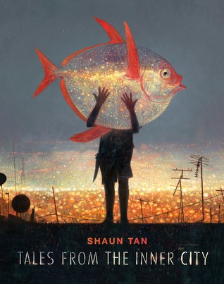 A man holding a giant fish with city lights in the background
