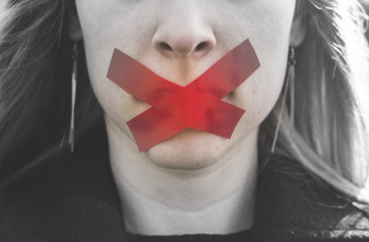 Woman with red tape over mouth