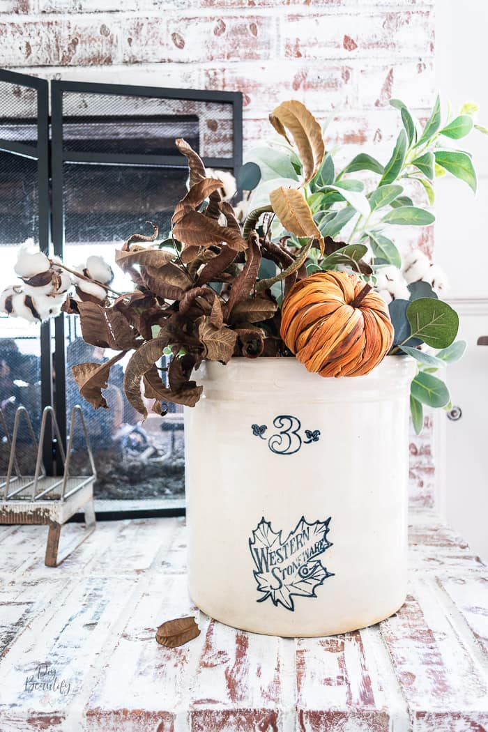 vintage pickle crock filled with fall leaves, cotton stems and pumpkins