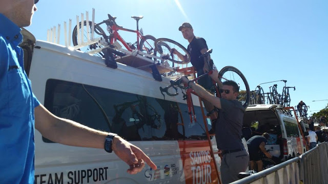 Two team staff members are bringing bikes down from the roof of a bus. One man is up the ladder on the side of the bus with a wheel in hand. His team mat is standing in front holding a bicycle frame with its front wheel missing in his outstretched arms.