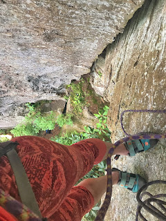 feet wearing climb shoes and a crack in the rock