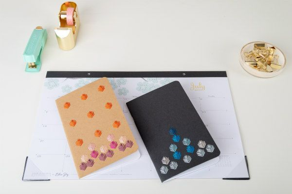 two notebooks with embroidered covers on desktop with desk accessories
